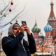Ein Mann macht Fotos auf dem Roten Platz mit der Basilius-Kathedrale im Hintergrund.