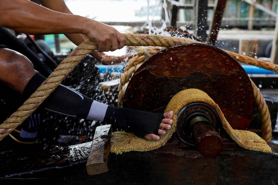 Ein Arbeiter zieht an einer Seilwinde.