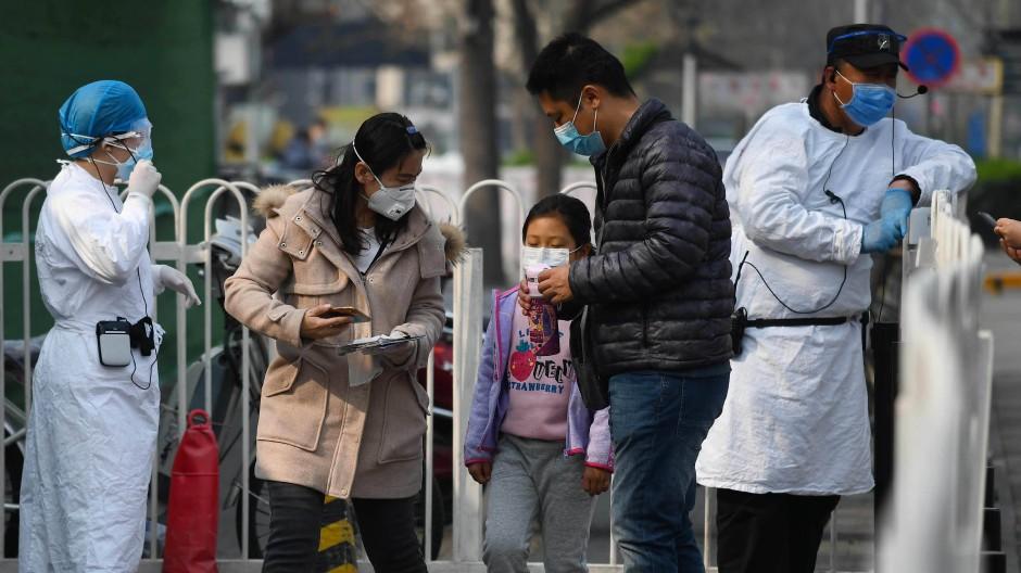 Eine chinesische Familie in Peking bei einer Kontrolle vor einem Kinderkrankenhaus Ende März