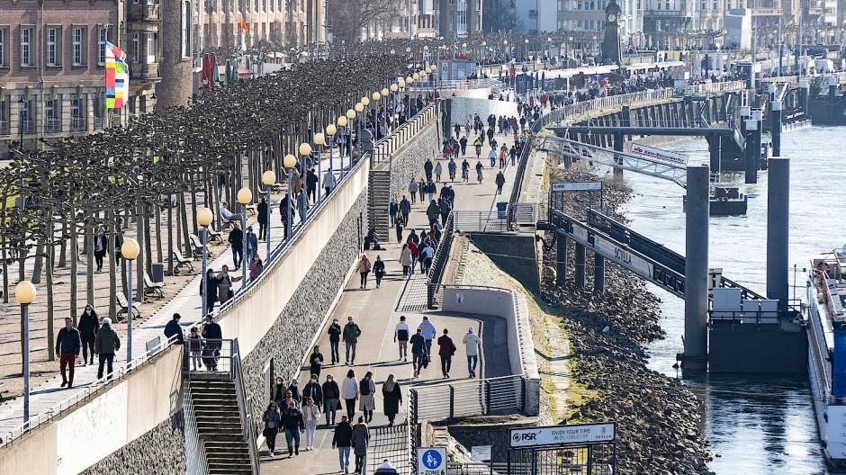 Menschen gehen am Sonntag bei Sonnenschein am Rheinufer in Düsseldorf spazieren.