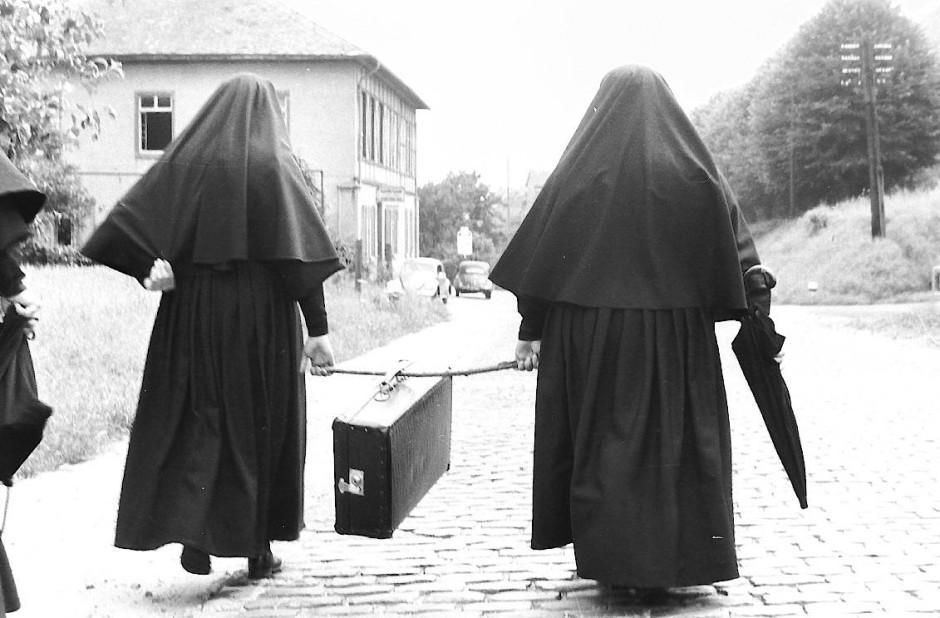 Zwei Dernbacher Schwestern sind auf dem Weg vom Kloster Tiefenthal nach Martinsthal im Rheingau. Damals, im Jahre 1952 war die Schlangenbader Straße gepflastert und noch wenig befahren. Es fuhr auch ein kleines Bähnchen bis nach Schlangenbad. In dem Haus links im Bild befand sich ein Lokal (Tiefenthal). Später befand sich darin eine Zahnarztpraxis die auch manch einer Schwester aus dem Kloster manch einen Zahn ziehen musste.