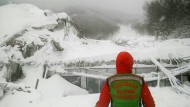 Eine Rettungskraft steht am Donnerstag auf Skiern vor dem eingestürzten Hotel.