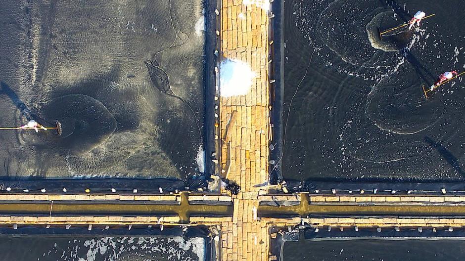 Menschen arbeiten in den Salzteichen eines Salzwerks im chinesischen Putian.