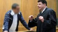 Der Angeklagte spricht am Donnerstag mit seinem Verteidiger im einem Gerichtssaal des Landgerichts in Hannover.