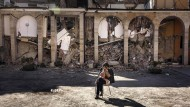 Bild der Verzweiflung: Eine Frau sitzt am Freitag vor einem zerstörten Konvent in Amatrice.