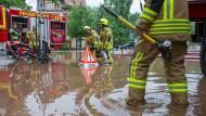 Feuerwehrleute pumpen am Sonntag Wasser aus einem Hof in Ilmenau (Thüringen). Zu den Überschwemmungen kam es auch, weil die Gewitter ungewöhnlich langsam weitergezogen sind.