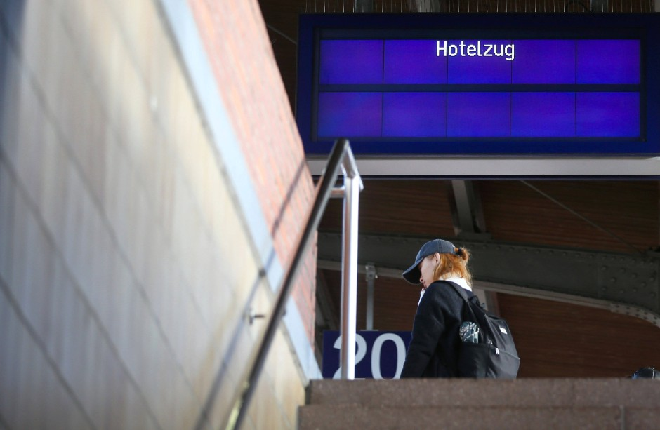 Eine Reisende steht am Sonntag im Bahnhof von Dortmund unter einer Anzeigetafel für einen Hotelzug.