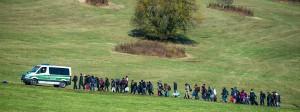 Flüchtlinge gehen nahe Wegscheid in Bayern im Oktober 2015 hinter einem Fahrzeug der Bundespolizei her.
