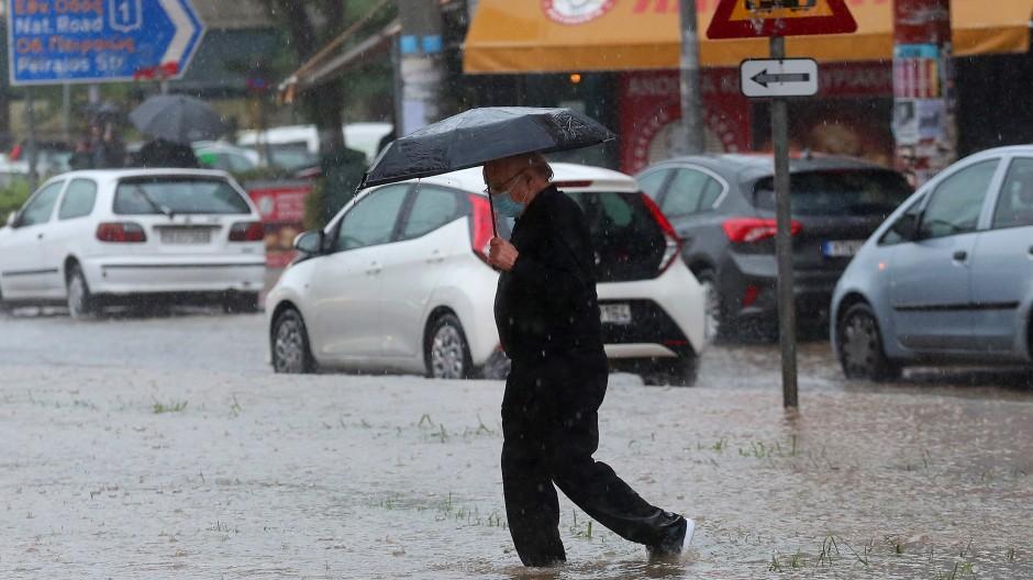 Ein Mann läuft durch die überschwemmten Straßen in Athen.