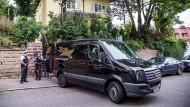 Ein Leichenwagen steht am Montag vor der Stuttgarter Anwaltskanzlei. Die dort gefundenen Männer wurden jetzt identifiziert.