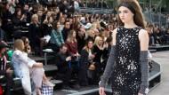 """CHANEL: Diese Schau ist nicht abgehoben. """"Major Karl"""" weiß, warum er die 37 Meter hohe Rakete in den Grand Palais hat stellen lassen. """"Die Raumfahrt war immer ein Zeichen von Modernität"""", sagt Karl Lagerfeld nach der gigantischen Schau mit sage und schreibe 90 Models. Und so ist das dann auch mit der Chanel-Mode: Die Farben sind vom Mond abgeschaut, die Glitzerstickereien auf schwarzen Kleidern sehen aus wie Galaxien, die silbernen Handschuhe könnten für einen Außenbordeinsatz taugen, und auf die runden Kragen könnte man fast einen Astronautenhelm setzen. Der Designer, der die Sucht der Schauen-Klientel nach Events kennt, belässt es natürlich nicht dabei: Am Ende hebt die Trägerrakete wirklich ein paar Meter ab, und die Models stehen im Bann des Rückstoßes und im Rauch der Brennstoffzündung."""