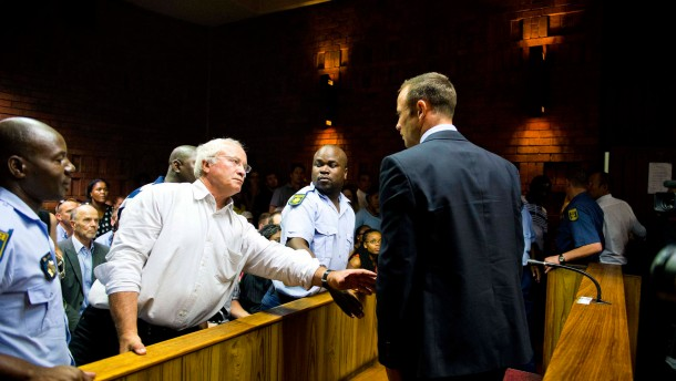 "South African ""Blade Runner"" Oscar Pistorius talks to his father Henke after his court appearance in Pretoria"