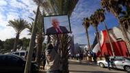 Im Gazastreifen hängt ein Mann ein Porträt von Palästinenserpräsident Abbas auf.
