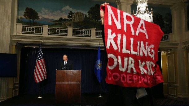 """Während der Rede des geschäftsführenden stellvertretenden NRA-Präsidenten Wayne Lapierre hält eine Demonstrantin ein Transparent mit der Aufschrift """"Die NRA tötet unsere Kinder"""" in die Kameras."""