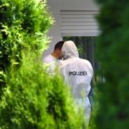 Zwei Polizisten stehen am Freitag in Unterschach bei Ravensburg vor dem Haus, in dem ein Mann einen Dreifachmord begangen haben soll.