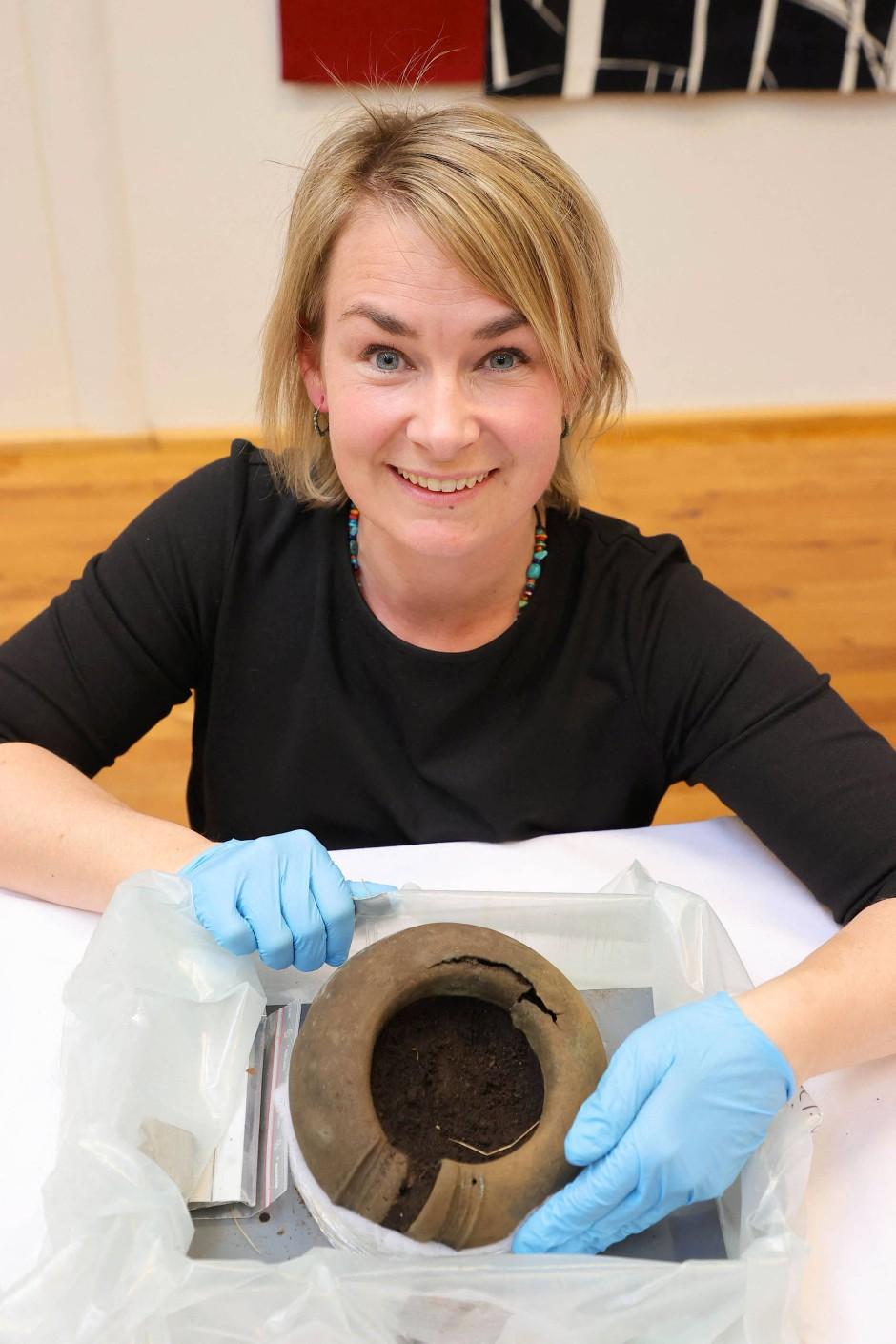 Konservatorin Madelene Skogbert zeigt einen Fußring aus Bronze.