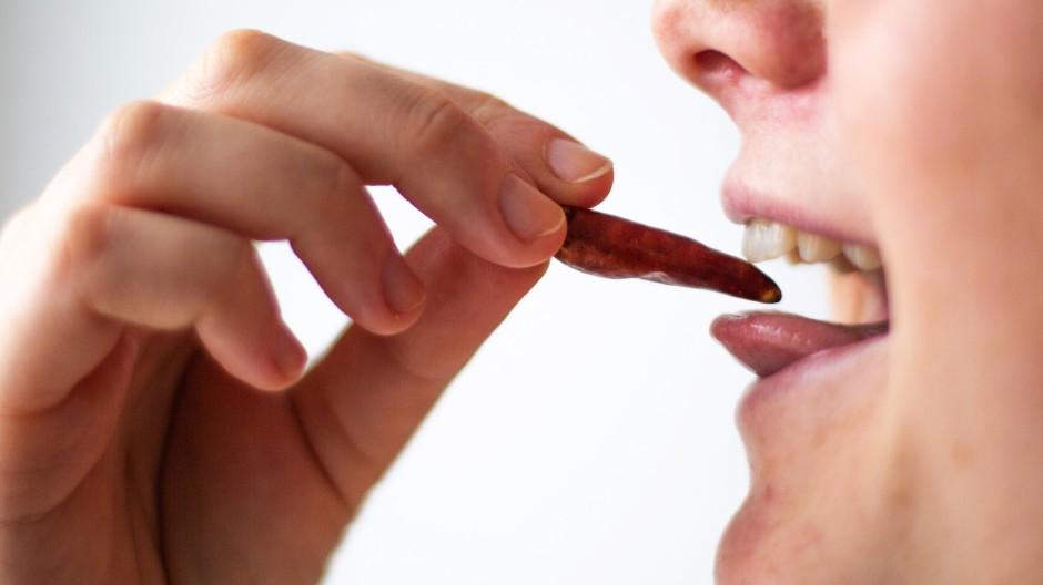 Die Substanz Capsaicin in Chilischoten hinterlässt einen starken Schmerz in Form eines heißen Brennens im Mund.