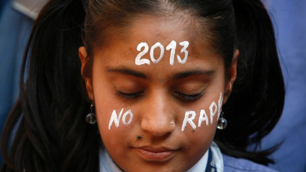 A student prays during a vigil for a gang rape victim, who was assaulted in New Delhi, in Ahmedabad