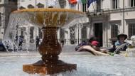 Touristen kühlen sich an einem Brunnen in Rom ab (Archivaufnahme).