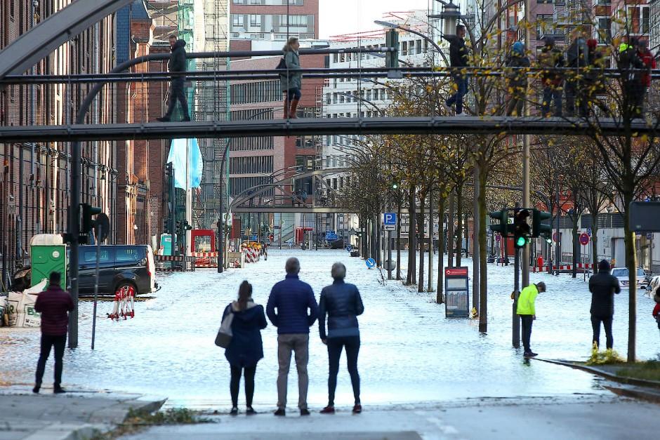 Passanten stehen vor einer überfluteten Straße in der Hafencity in Hamburg.
