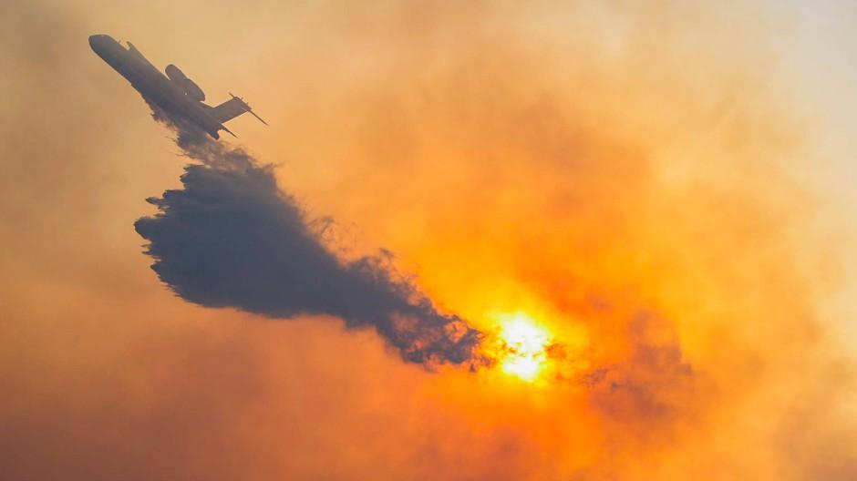 Ein Flugzeug fliegt Mitte Juli für Löscharbeiten über ein brennendes Waldgebiet auf der östlichen Ägäis-Insel Samos.