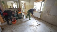 Erste Schritte: Luitpold Weinberger (rechts) säubert einen Wohnraum seines Hauses im Deggendorfer Ortsteil Fischerdorf (Bayern) vom Hochwasser