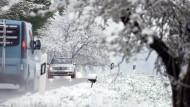 Neuschnee im April: Autos fahren am 1Mittwoch bei Grünkraut in Baden-Württemberg auf einer schneebedeckten Straße.