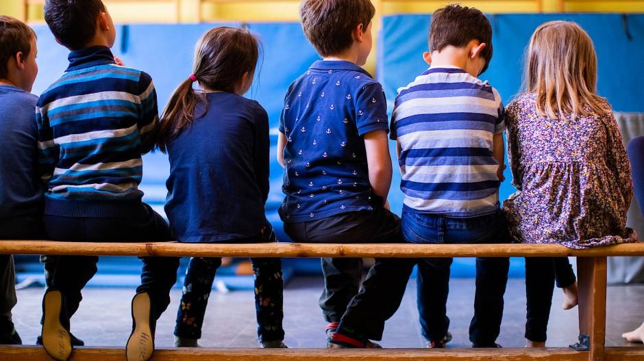 Warten auf ihren Einsatz: Kinder sitzen in einer Kita beim Sport auf der Bank.