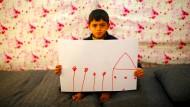 Ein großes Haus mit Blumen im Garten – der neun Jahre alte Ali Addahar zeigt eine Zeichnung seiner syrischen Heimat.
