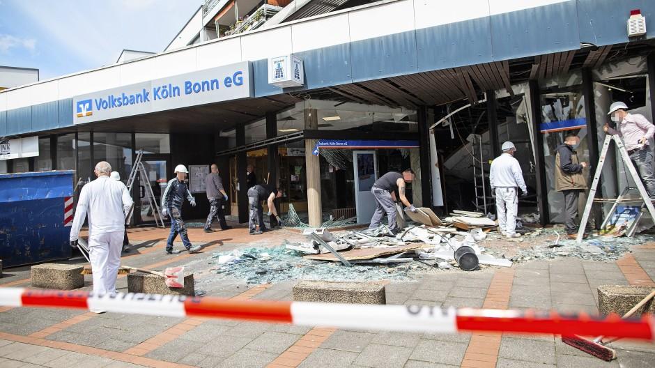 Arbeiter räumen nach der Sprengung eines Geldautomaten vor einer Bankfiliale auf.