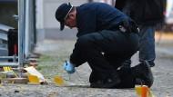Ein Polizist sichert am Mittwochmorgen nach dem Tod eines jungen Mannes am Tatort in der Genthiner Straße im Stadtteil Tiergarten Spuren.
