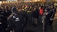 Polizisten umringen an Silvester eine Gruppe südländisch aussehender junger Männer.