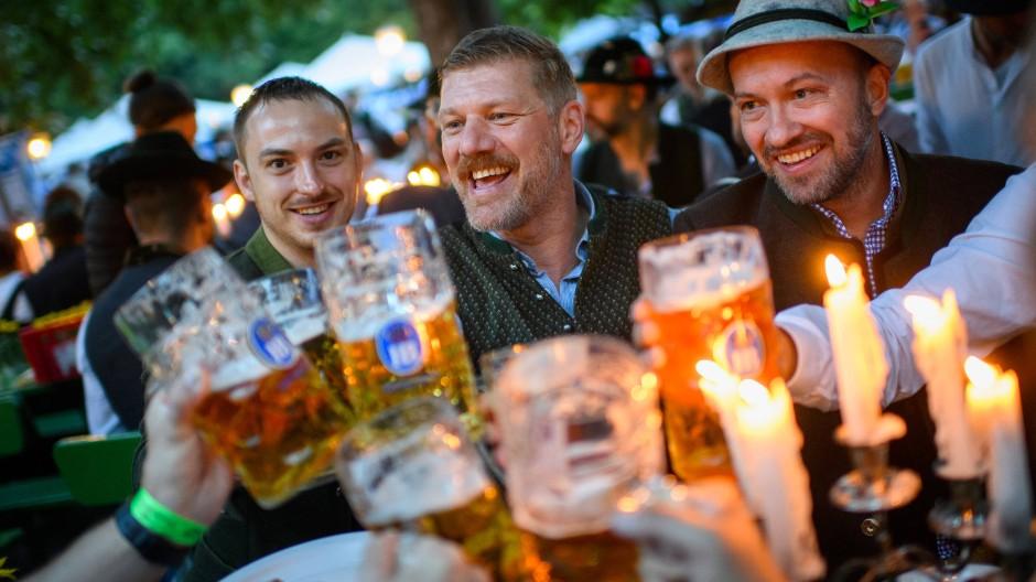 Junge Männer in Trachten prosten sich Ende Juli im Biergarten am Chinesischen Turm im Englischen Garten in München zu.