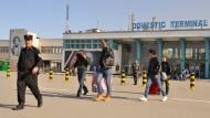 Eine Gruppe abgeschobener junger Afghanen verlässt im Februar 2017 in Begleitung eines Polizisten das Flughafengebäude in Kabul.