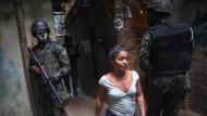 Vermummte Soldaten mustern eine Bewohnerin der Favela Rocinha im Süden von Rio de Janeiro