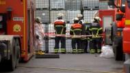 Feuerwehrmänner am Montag vor der Lagerhalle, in der Tausende Liter Säure ausgelaufen sind.  Bis zum Ende des Einsatzes sollen Fenster geschlossen bleiben.