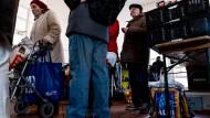 Viele ältere Frauen müssen sich Nahrungsmittel bei der Tafel besorgen – hier eine Dame mit Rollator im März 2018 bei einer Frankfurter Tafel.
