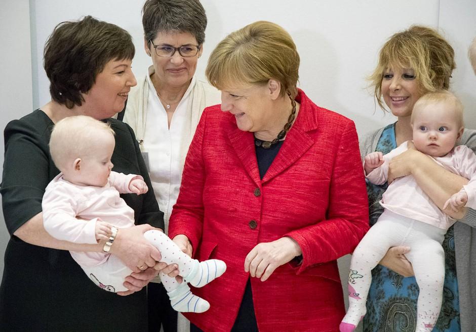 Auch die Politik kümmert sich verstärkt um Familien: Bundeskanzlerin Angela Merkel schaut sich Anfang März in Berlin Drillingsmädchen bei einer Festveranstaltung einer Kinderhilfsorganisation an, die Ehrenamtliche zur Entlastung junger Eltern bei der Betreuung ihrer Kinder vermittelt.