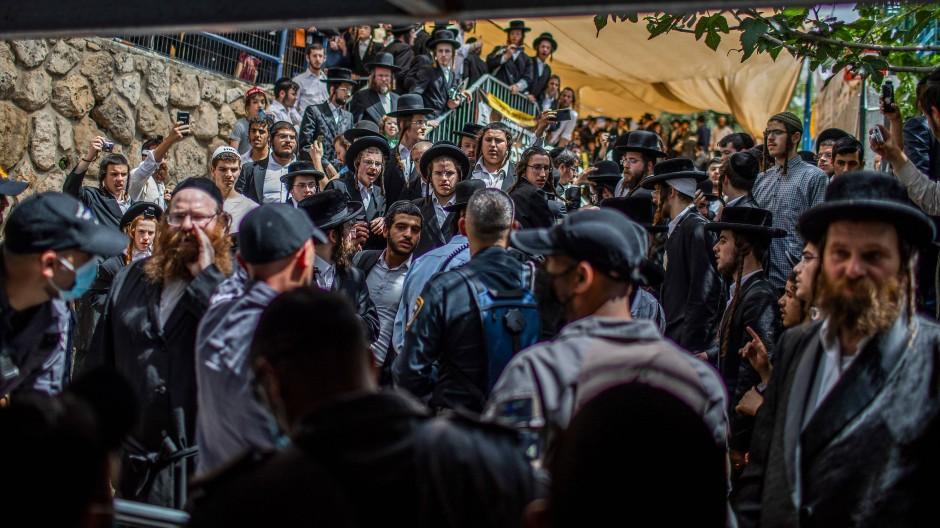 Orthodoxe Juden haben sich vor Sicherheitskräften an der Pilgerstätte auf dem Berg Meron versammelt, wo am frühen Freitag Dutzende Gläubige bei einer Massenpanik getötet wurden.