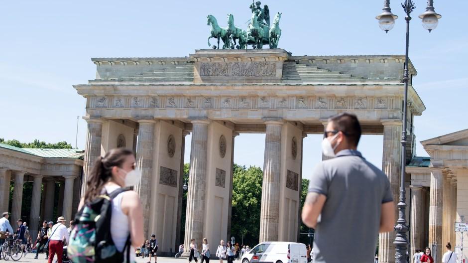 Touristen stehen im Juni vor dem Brandenburger Tor in Berlin.