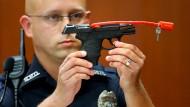 """Ein Polizeioffizier mit der Waffe, mit der George Zimmermann Trayvon Martin erschoss. Jetzt wird sie als """"Stück amerikanischer Geschichte"""" versteigert."""