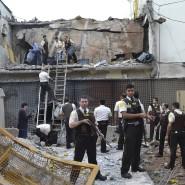 Polizisten und Prosegur-Wächter untersuchen am Montag in Ciudad del Este die Überreste des Lagers eines Geldtransport-Unternehmens, das von mehr als 60 schwerbewaffneten Verbrechern angegriffen wurde.