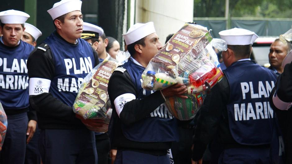 """Arbeiter der Hilfsorganisation """"Plan Marina"""" eröffnen eine Sammelstelle, an der Bürger für die Opfer des Erdbebens spenden können."""
