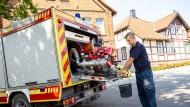 Einsatzkräfte der Freiwilligen Feuerwehr Lauenau zapfen Löschwasser aus dem Tank eines ihrer Einsatzfahrzeuge, um die trocken gelegte Gemeinde damit zu versorgen.