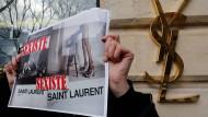 """Aktivisten halten vor einem Saint-Laurent-Geschäft in Paris Bilder der umstrittenen Werbung mit dem Schriftzug """"sexistisch"""" darauf in die Luft."""
