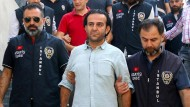 Bülent Mumay (Mitte) und andere türkische Journalisten wurden am Freitag von Polizisten ins Gericht geleitet.
