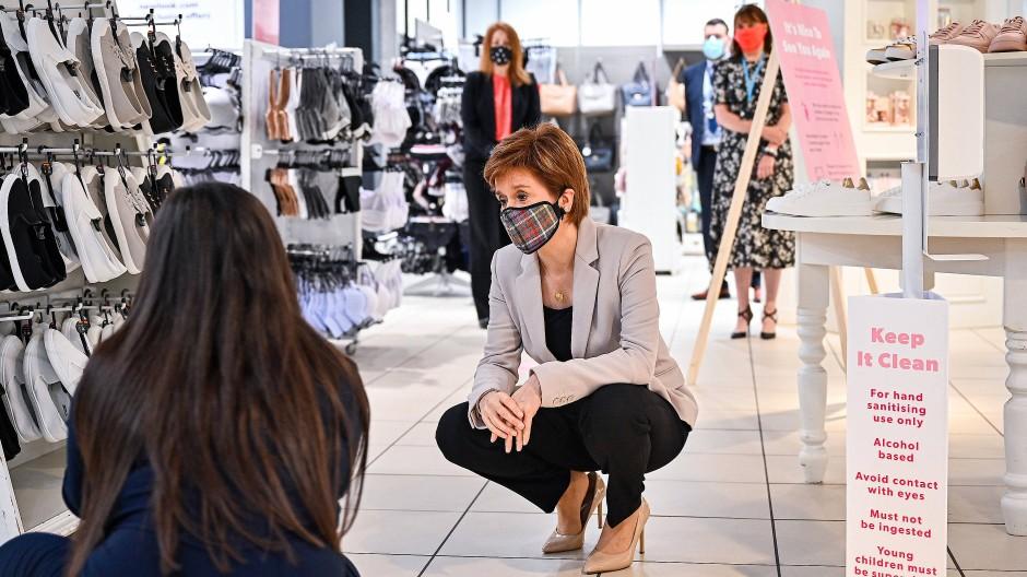 Die schottische Regierungschefin Nicola Sturgeon trägt eine Maske mit Tartanmuster während eines Besuchs im Einkaufszentrum in Edinburgh.
