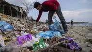 Ein Student sammelt Plastikmüll vom Strand in Ujong Blang in Indonesien.