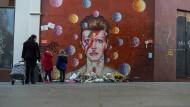 Eine Frau steht am Freitag mit ihren Kindern vor dem Wandgemälde von David Bowie in Brixton in London. In einer zweitägigen Auktion werden bei Sotheby's Kunstwerke aus der privaten Kunstsammlung des verstorbenen Musikers versteigert.