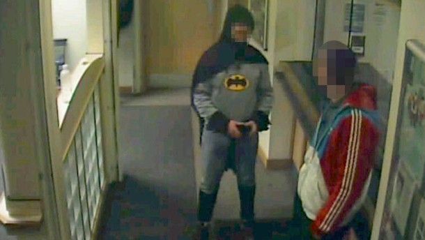 A man dressed as Batman and a burglary suspect stand in a police station in Bradford, northern England